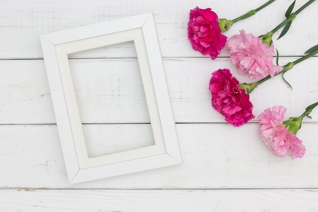 Mieszkanie lay puste miejsce rama dla kopii przestrzeni z goździkiem kwitnie białego drewnianego tło