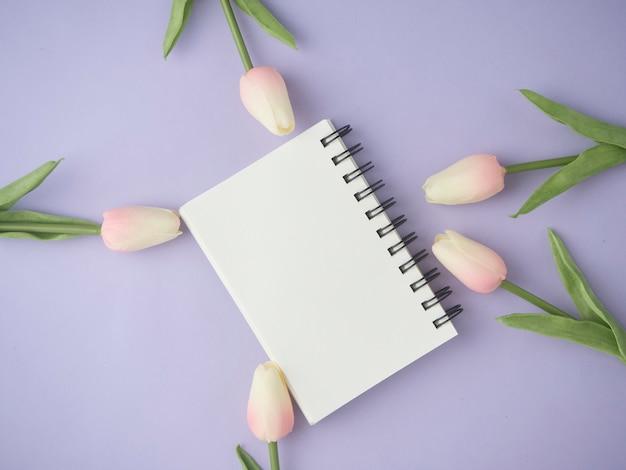 Mieszkanie lay różowe kwiaty tulipanów na fioletowym tle z pustego notatnika.