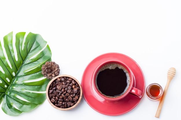 Mieszkanie leżał czerwony kubek kawy i ziarna kawy w misce z drewna na białym tle