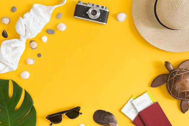Mieszkanie leżał i widok z góry akcesoria podróżnika na żółtym tle z miejsca kopiowania. koncepcja podróży, tropikalnej podróży i wakacji. tło lato.