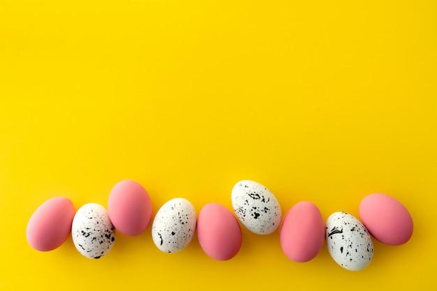 Mieszkanie leżał widok z góry białych i różowych jaj z minimalnymi wzorami na żółtym tle