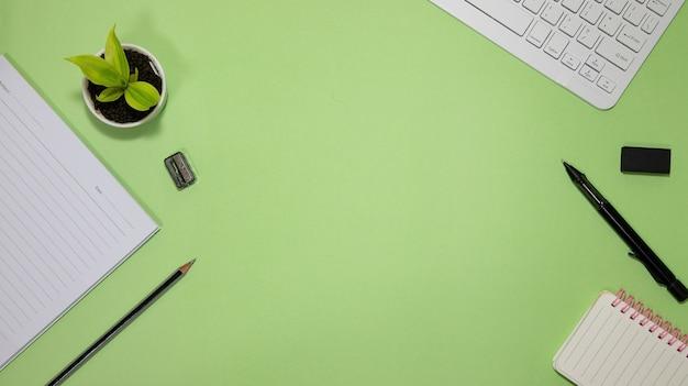Mieszkanie leżało na czarno do koncepcji szkoły i edukacji na zielonym tle z pustym notatnikiem, klawiaturą, zieloną rośliną i dostawami.