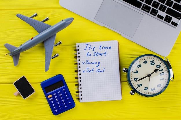 Mieszkanie leżało nowe plany i koncepcja biznesowa. notatnik z celami, laptopem, budzikiem, kalkulatorem i samolocikiem na żółtym drewnie.