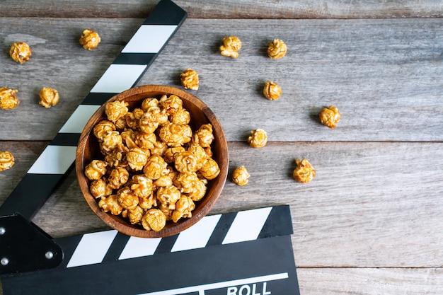 Mieszkanie leżało smaczny karmelowy popcorn i clapperboard na drewnianym stole, odgórny widok, kopii przestrzeń. koncepcja czasu filmu