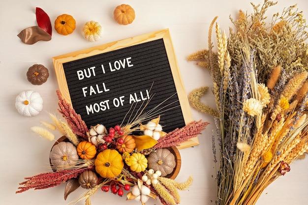 Mieszkanie leżało z filcową tablicą na listy i tekstem ale najbardziej kocham jesieńjesienna dekoracja stołu kwiatowy wystrój wnętrz na jesienne wakacje z ręcznie robionymi dyniamiflatlay, widok z góry