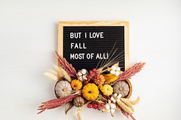 Mieszkanie leżało z filcową tablicą z literami i tekstem ale najbardziej kocham spadać. jesienna dekoracja stołu. kwiatowy wystrój wnętrz na jesienne wakacje z ręcznie robionymi dyniami. flatlay, widok z góry