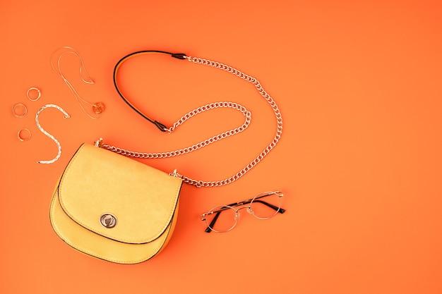 Mieszkanie leżało z kobiecymi akcesoriami w żółtym kolorze na pomarańczowej skórzanej ścianie z teksturą. moda, internetowy blog o urodzie, letni styl, zakupy i koncepcja trendów