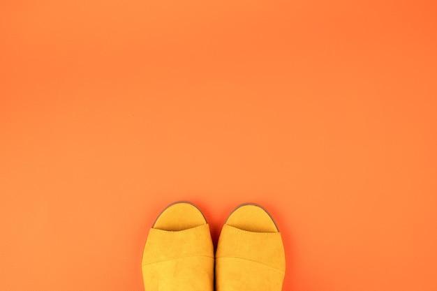 Mieszkanie leżało z kobietą w kolorze żółtych letnich butów na pomarańczowej skórzanej ścianie. moda, internetowy blog o urodzie, letni styl, zakupy i koncepcja trendów