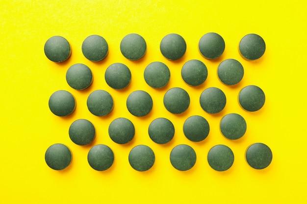 Mieszkanie leżało z pigułkami spiruliny na żółtym tle, widok z góry