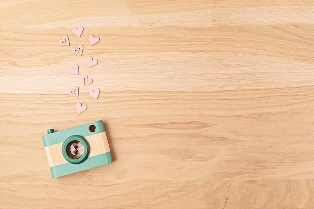 Mieszkanie leżało z zabawkowym drewnianym aparatem i sercami na drewnianej ścianie. media społecznościowe, posty, polubienia, obserwujący, koncepcja zajęć z fotografii online. widok z góry, miejsce na kopię.