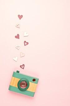 Mieszkanie leżało z zabawkowym drewnianym aparatem i sercami na różowej ścianie. media społecznościowe, posty, polubienia, obserwujący, koncepcja zajęć z fotografii online. widok z góry, miejsce na kopię.