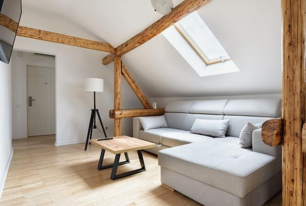 Mieszkanie na poddaszu nowoczesny salon ze starymi rustykalnymi drewnianymi belkami