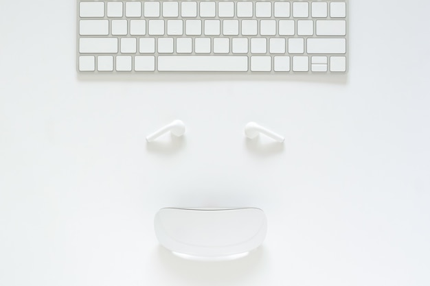 Mieszkanie nieatutowy klawiatura, słuchawki i mysz ustawiający jako uśmiechnięta twarz na białym tle dla cyber poniedziałku sprzedaży online pojęcia.