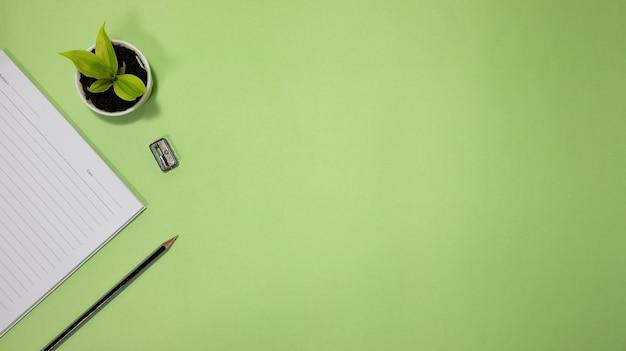 Mieszkanie świeckich czarny do koncepcji szkoły i edukacji na zielonym tle z pustym notatnikiem, ołówkiem, zieloną rośliną i dostawami.