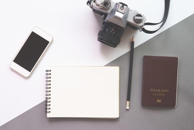 Mieszkanie świeckich projekt biurko z notebooka, okulary, aparat fotograficzny, smartphone i paszport na białym tle.