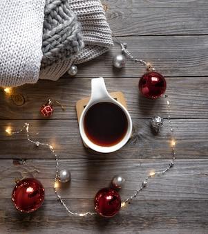 Mieszkanie świeckich świątecznych kompozycji z filiżanką herbaty na drewnianym tle.
