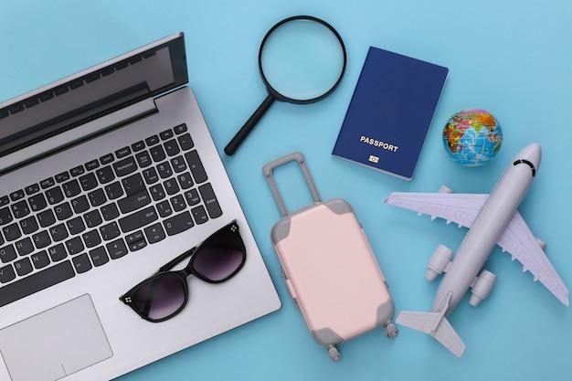 Mieszkanie świeckich wakacje wakacje i koncepcja planowania podróży. akcesoria do laptopów i podróży na niebieskim tle. widok z góry