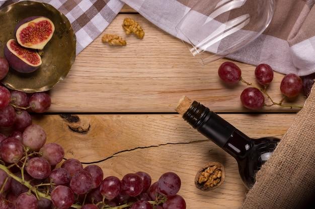 Mieszkanie z burzą czerwonych winogron, butelką wina, kieliszkiem i figami