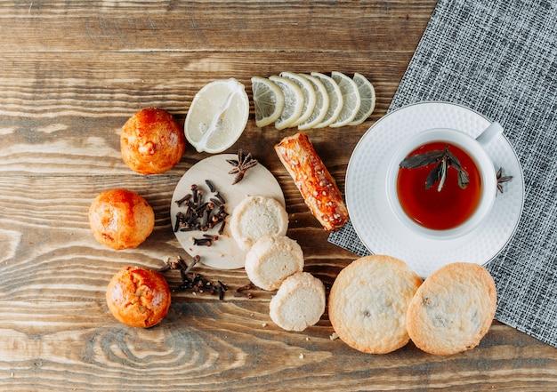Miętowa herbata w filiżance z plasterkami cytryny, herbatniki, goździki widok z góry na drewnianym stole