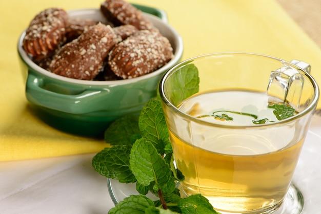Miętowa herbata w przezroczystym kubku ze słodkimi ciasteczkami