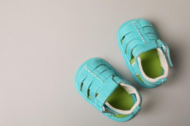Miętowe sandały niemowlęce na jasnoszarym tle.