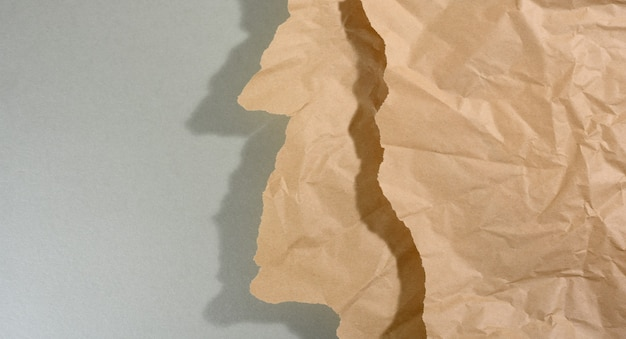 Miętowo-brązowy kawałek papieru z podartymi krawędziami i cieniem na szarym tle. abstrakcyjne kreatywne tło dla projektanta, kopia przestrzeń