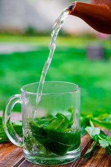 Miętowy herbaciany dolewanie w szklaną filiżankę na drewnianym stole w ogródzie i na naturze.