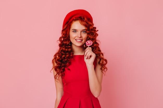 Migawka niebieskookiej rudej kobiety w eleganckiej sukience i stylowym kapeluszu, uśmiechnięta i trzymająca lizaka.