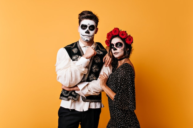 Migawka pary z grafiką twarzy na dzień wszystkich zmarłych. młoda kobieta z koroną róż przytula ciemnowłosego faceta.