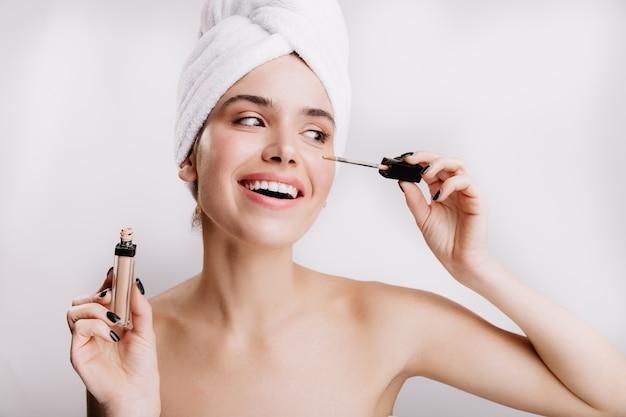Migawka ślicznej dziewczyny w ręcznik na odizolowanej ścianie. pani robi makijaż dzienny.