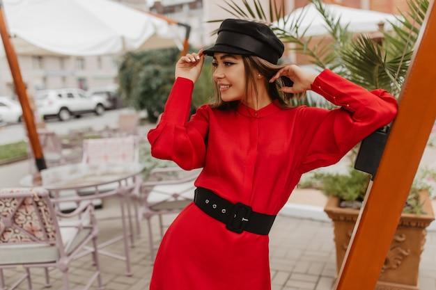 Migawka w paryskim stylu młodej fashionistki. dziewczyna z wygodną krótką fryzurą odważnie pozuje do zdjęcia ulicy