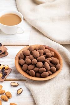Migdał w czekoladowych drażetkach w drewnianym talerzu i filiżankę kawy na białym tle drewniane i lnianą tkaniną. widok z boku, z bliska.