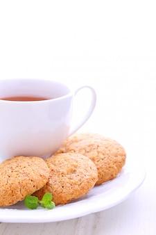 Migdałowi ciastka w białym talerzu z filiżanką herbata