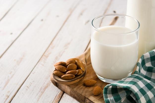 Migdałowy mleko w szkle i butelce na białym drewnianym stole. skopiuj miejsce
