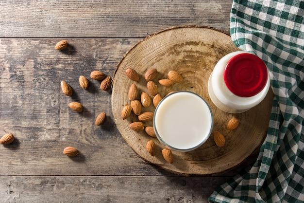 Migdałowy mleko w szkle i butelce na drewnianym stole. widok z góry.