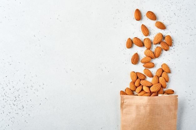 Migdałowy orzech w papierowej torbie na białym tle. przekąska wegańskie jedzenie bez cukru.