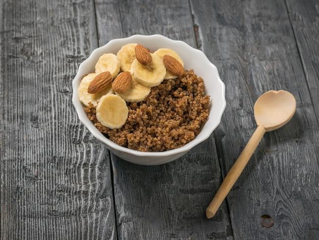 Migdały i plastry banana w misce owsianki z komosy ryżowej i kakao. zdrowa dieta.