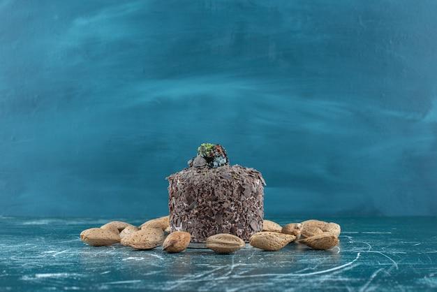 Migdały łuskane wokół małego ciasta na niebiesko.