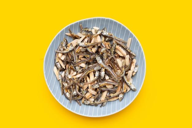 Migdały mixed anchovy w płytce na żółtym tle.
