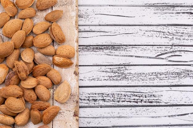 Migdały na drewnianej desce tekstury po lewej stronie biały drewniany