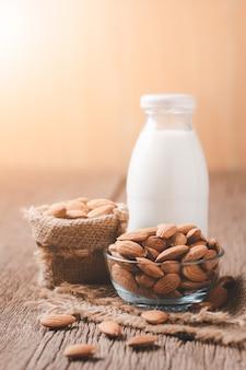 Migdały orzechy w szklanej misce i butelkę świeżego mleka na stół z drewna