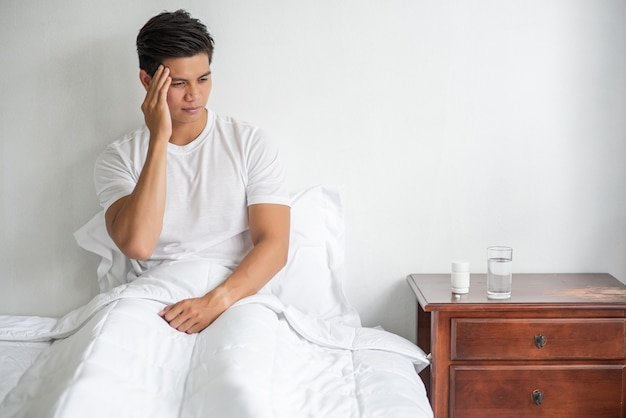 Migrena mężczyzna, ręka dotykająca głowy, siedzący w łóżku.