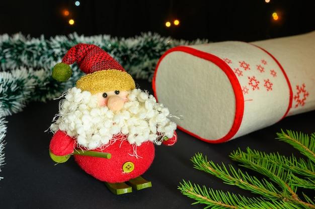 Mikołaj i filcowy but z prezentami dla dzieci. boże narodzenie i nowy rok koncepcja na czarnym tle.