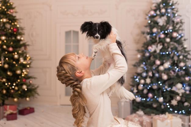 Mikołaj podarował dziewczynie psa na boże narodzenie. świąteczna opowieść. szczęśliwe dzieciństwo. pierwsze zwierzątko.