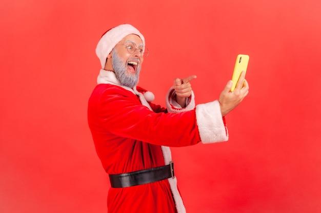 Mikołaj stojący z inteligentnym telefonem wskazującym na wyświetlacz, patrzący z uśmiechem.