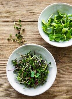Mikro zieleni w miseczkach na starym drewnianym tle, mikro zielona, koncepcja zdrowej żywności