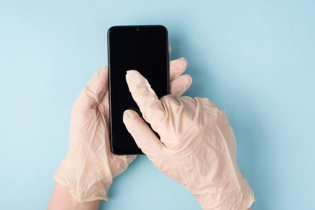 Mikroby na koncepcji smartfona. pov top overhead zbliżenie widok zdjęcia rąk w rękawiczkach pisania sms-ów na telefonie na białym tle niebieskim tle