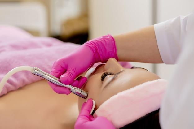Mikrodermabrazja diamentowa, peeling kosmetyczny. kobieta podczas zabiegu mikrodermabrazji w salonie piękności
