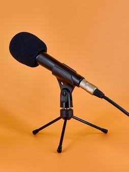 Mikrofon dynamiczny na trójnogu z gąbką ochronną.