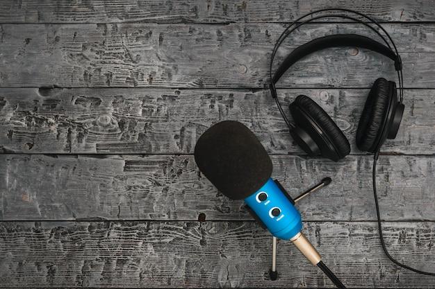 Mikrofon i słuchawki na czarnym drewnianym stole.